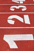 Red running track with white numbers on it — Fotografia Stock