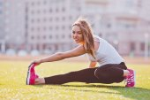 Sporty beautiful girl in sportswear stretching on a field in front of her uiversity campus — Stock Photo