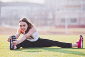 Young woman stretching her foot while performing splits on a field on a sunny summer day — Stock Photo