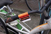 Cycling inconvenience, remove sticker on bike in downtown Amster — Stock Photo