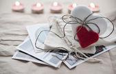 Biscotto allo zenzero sdraiato sulle cartoline per San Valentino con candele accese su sfondo a forma di cuore bianco zenzero. — Foto Stock