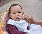 Baby eating food by spoon — Stock Photo