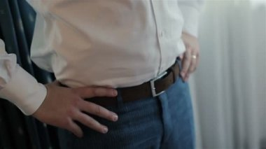 Groom cufflinks buttons on the sleeves, hands on his belt. Close-up. — Stock Video