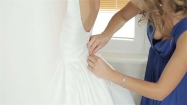 Bridesmaid helping Bride to button wedding dress — Stock Video