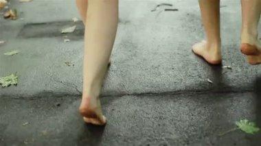 秋に濡れた道路で裸足で歩く 2 人。足のクローズ アップ — ストックビデオ