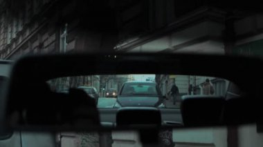 Rear view mirror reflection of evening street with buildings cars and passers-by — Stock Video