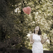 Happy Smiling Young Woman with a Red Shaped Heart Balloon — Stock Photo