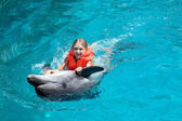 Happy Little Girl Riding the Dolphin in Swimming Pool — Stock Photo