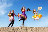 Three Cute Little Witches Jumping with Bags — Stock Photo