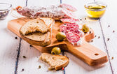 Slices of salami on a cutting board — Stock Photo