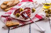 Slices of salami on a white plate — Stock Photo