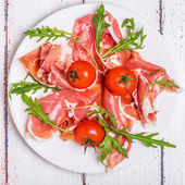 Prosciutto with arugula and cherry tomatoes  — Stock Photo