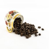 Overturned porcelain coffee cup with coffee beans isolated on white — Stock Photo