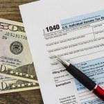 Formulário de imposto de renda individual dos Estados Unidos 1040 com caneta e dinheiro — Fotografia Stock  #68346383