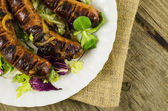 Roasted sausage on wooden table — Stock Photo