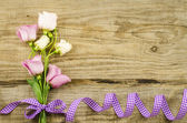 Empty wooden background with colorful flowers and purple ribbon — Stock Photo