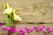 Empty wooden background with colorful flowers and pink ribbon — Stock Photo