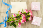 Empty postcard, flower and blue ribbon on wooden background — Stock Photo