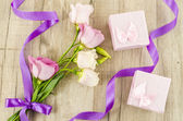 Pink flower and gift box on wooden background — Stock Photo