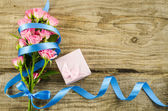 Empty wooden background with colorful flowers and blue ribbon — Stock Photo