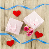 Gift box with rose flower, heart and ribbon on wooden background — Stock Photo