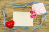 Empty postcard with rose flower, gift box, heart and ribbon — Stock Photo