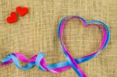 Heart shaped ribbon on linen background — Stock Photo