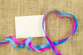Empty card with heart shaped ribbon on linen background — Stock Photo