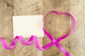 Empty card with heart shaped ribbon on wooden background — Stock Photo