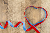 Heart shaped ribbon on wooden background — Stock Photo