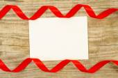 Empty card with red ribbon on wooden background — Stock Photo