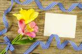 Empty card with flower and ribbon on wooden background — Stock Photo