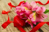 Pink flowers bouquet with heart on wooden table — Stock Photo