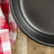 Folded tablecloth and frying pan on white wooden background — Stock Photo #71656133