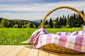 Picnic basket on wooden table — Stock Photo