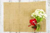 Flowers with heart on jute background — Stock Photo