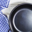 Folded tablecloth and frying pan on wooden background — Stock Photo #74033105
