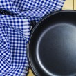 Folded tablecloth and frying pan on wooden background — Stock Photo #74035455