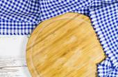 Cutting board with folded tablecloth on white wooden table — Stock Photo