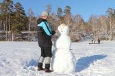The man building a snowman — Stock Photo