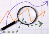 Graphs and Magnifying glass — Stock Photo
