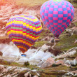 Colorful hot air balloons flying over rock landscape at Cappadoc — Stock Photo #68264917