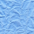 Wrinkled blue paper fragment as a background texture — Stock Photo #68604037