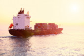 Container ship is sailing along the waterway during sunset.  — Stock Photo