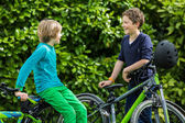Two boys in a garden with bikes — Stock Photo