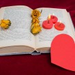 Three red candles lying on the book with red heart 2 — Stock Photo #63574311