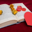Three red candles lying on the book with red heart — Stock Photo #63574313