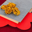 Four dried yellow roses lying on the book with two red hearts — Stock Photo #63574337
