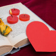 Three red candles lying on the book with paper heart — Stock Photo #63574597