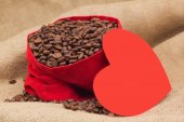 Red paper heart next to velvet red sac with coffee beans — Stock Photo